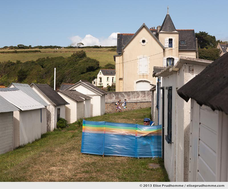 Bathing cabins and bathers on a sunny windy summer day on Ris Beach, Douarnenez, France, 2013 by Elise Prudhomme