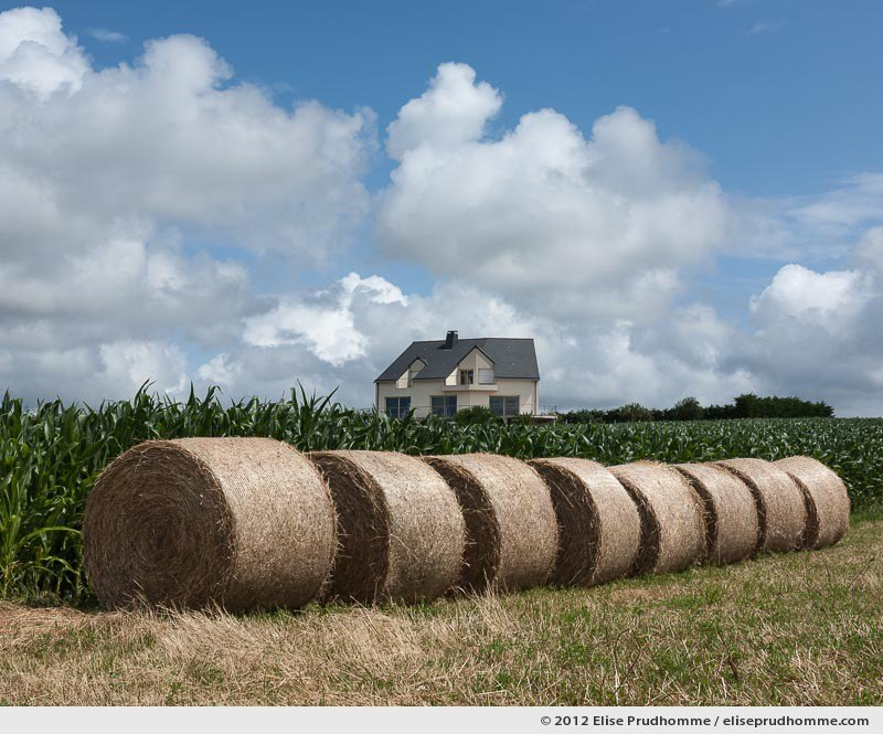 Prefab house and hay bales under a cloudy sky, Normandy, France, 2012 by Elise Prudhomme