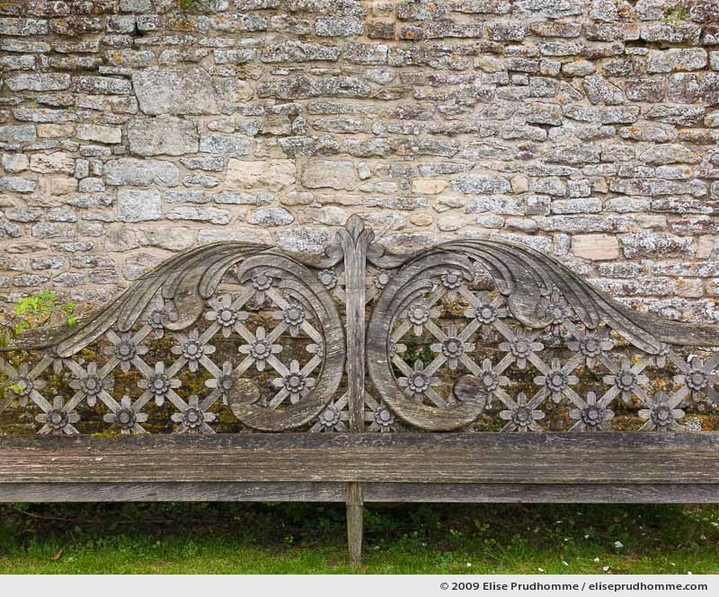 Carved wooden bench and stone wall, Brecy Castle Gardens, Saint Gabriel Brécy, France, 2009 (series Notable Gardens of France) by Elise Prudhomme.