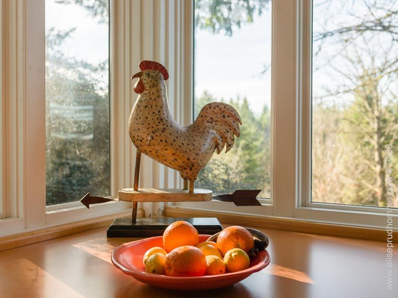 Kitchen interior detail of antique rooster weathervane and fruit bowl still life by Elise Prudhomme.