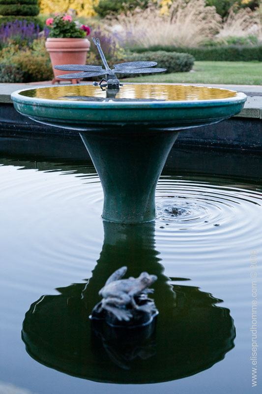 Metal fountain and pool in formal garden
