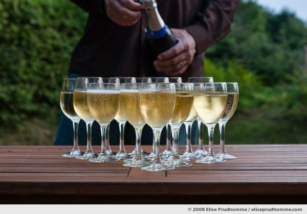 Glasses of champagne outside on a teck garden table, Normandy, France, 2008 by Elise Prudhomme