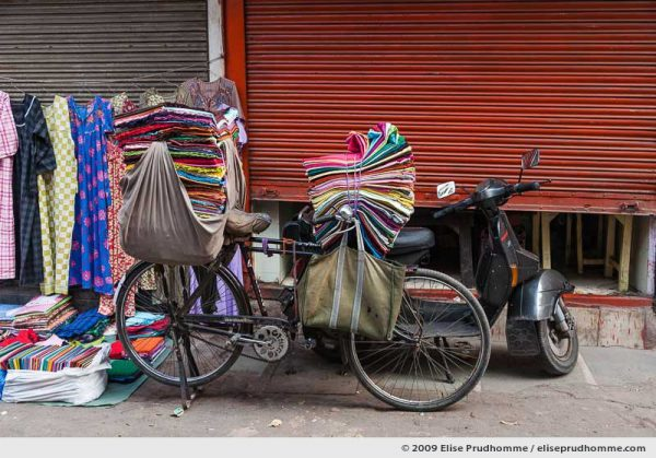 A bicycle piled high with textiles parked on a side street in Old Delhi, India, 2009 by Elise Prudhomme.
