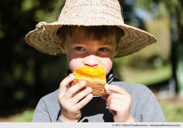 A young boy wearing a straw hat eats vanilla flan, Auvergne, France, 2011 by Elise Prudhomme.