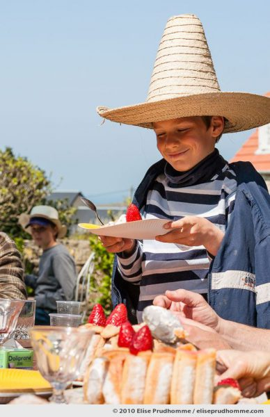 Smiling boy in a sombrero holding a paper plate with Strawberry Charlotte dessert, Normandy, France, 2010 by Elise Prudhomme.