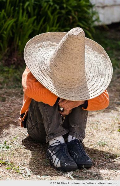 Boy sitting in a garden hidden under a sombrero, Normandy, France, 2010 by Elise Prudhomme.