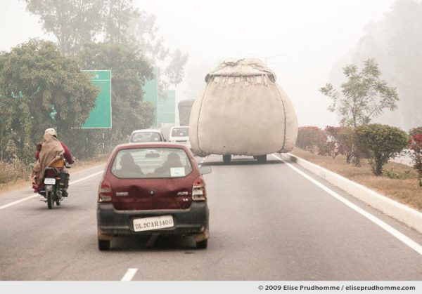 Cars, scooters and overloaded trucks on the Yamuna Expressway connecting Delhi to Agra, India, 2010 by Elise Prudhomme.