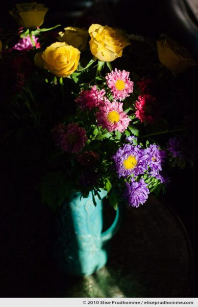 Multi-colored flowers and yellow roses in a turquoise vase in chiaroscuro lighting, Normandy, France, 2010 by Elise Prudhomme.