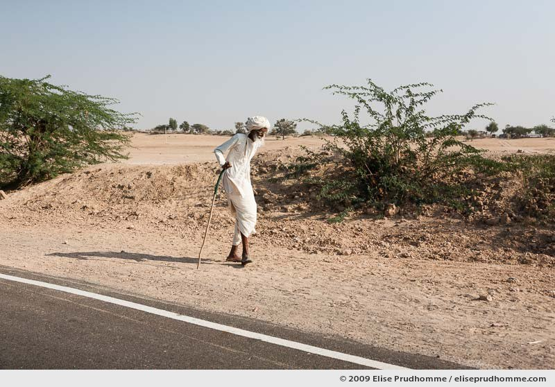 Elderly white-bearded man in traditional Bishnoi clothing walking along the roadside, Rohet, India by Elise Prudhomme.