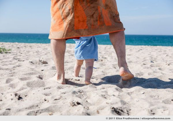 Father and baby walking on beach sand towards the ocean, Fermanville, France, 2011 by Elise Prudhomme.