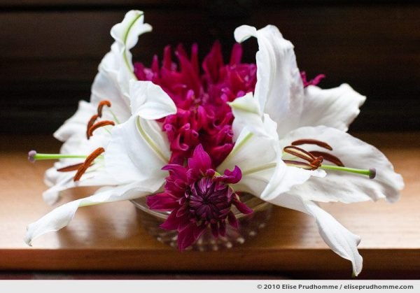 Flower arrangement of white lilies and magenta-colored dahlias on a table, Normandy, France, 2010 by Elise Prudhomme.