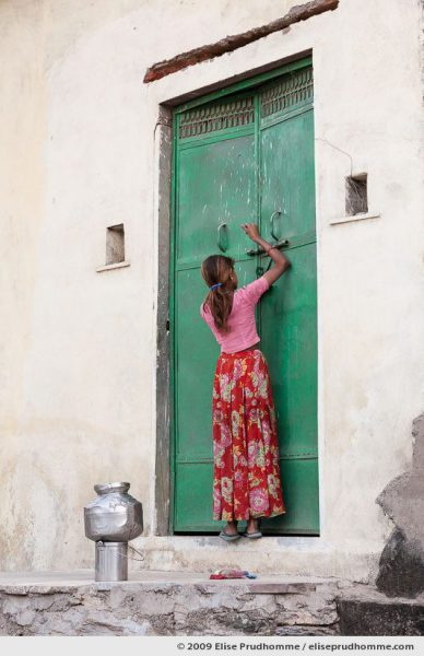 Girl in a rural Indian village latching the door of her home before collecting water from a communal well, Delwara, Rajasthan, Northern India, 2009.