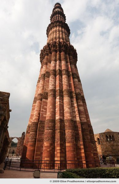 Low angle full vertical view of Qutub Minar tower under cloudy skies, Delhi, India, 2009 by Elise Prudhomme.