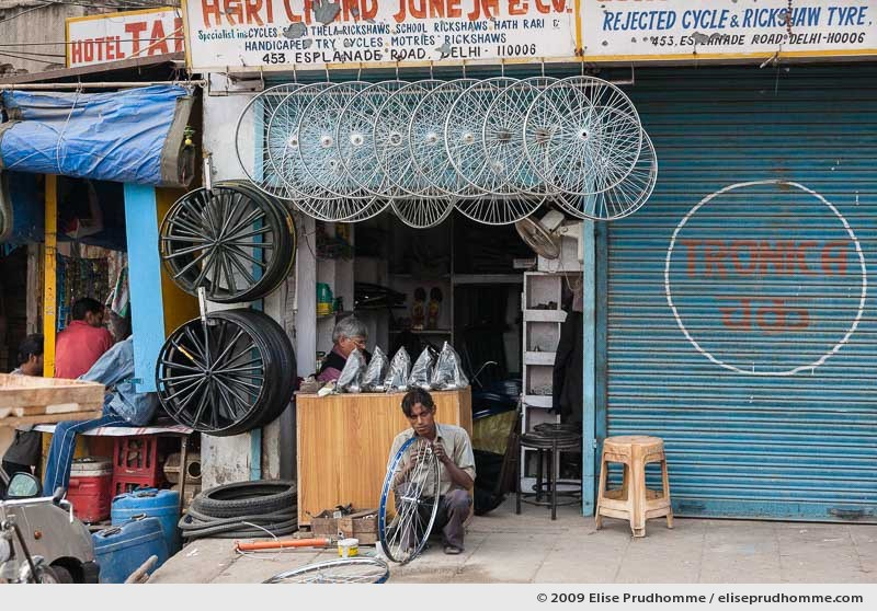 Man repairing a bicycle wheel in front of a repair shop on Esplanade Road, Delhi, India, 2009 by Elise Prudhomme.