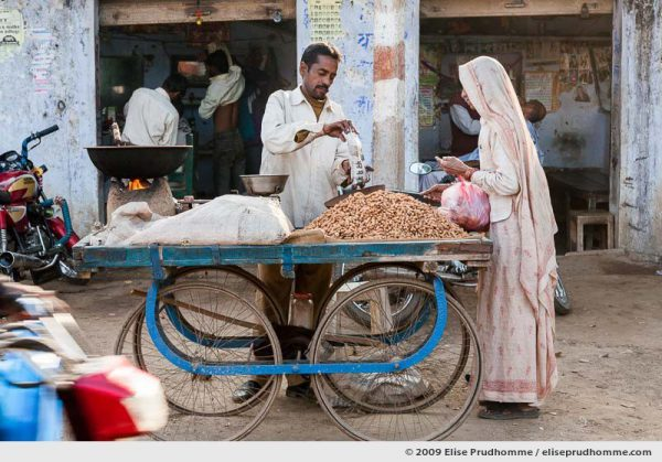 Man selling peanuts to a woman customer in a rural village, Rajasthan, India, 2009 by Elise Prudhomme.