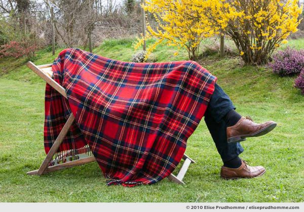 Man sleeping in a folding garden chair under a plaid blanket, Normandy, France, 2010 by Elise Prudhomme.