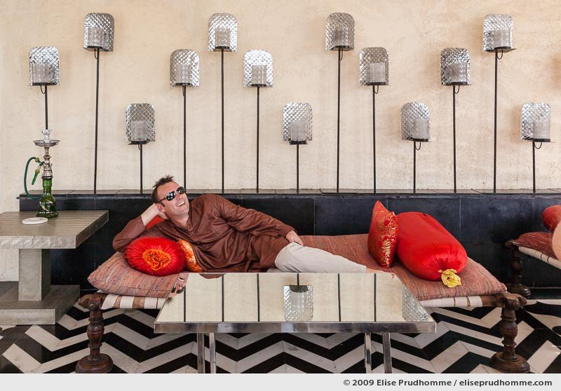 Middle-aged Caucasian man wearing an Indian tunic and sunglasses relaxing on sofa in Devi Garh Resort Hotel, Delwara, India, 2009 by Elise Prudhomme.