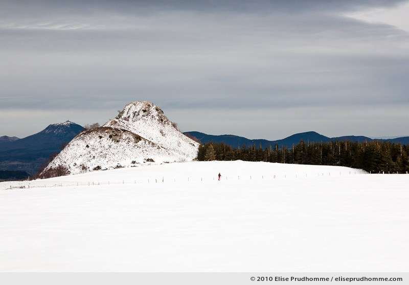 One cross-country skier and the Puy-de-Dôme in the distance, Banne d'Ordanche, Auvergne, France, 2010 by Elise Prudhomme.