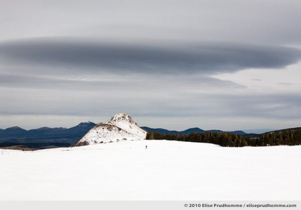 One person cross-country skiing with the Puy-de-Dôme in the distance, Auvergne, France, 2010 by Elise Prudhomme.