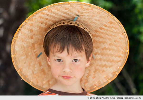 Portrait of a brown-eyed boy wearing a bamboo rain hat, Normandy, France, 2010 by Elise Prudhomme.