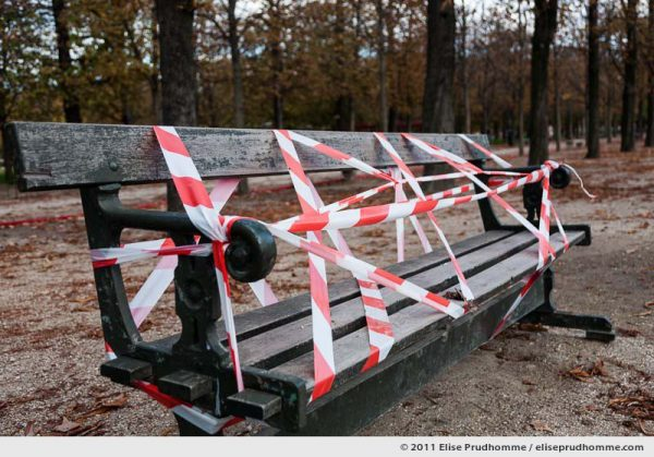 Public bench covered in red and white boundary tape, Jardin des Tuileries, Paris, France, 2011 by Elise Prudhomme.