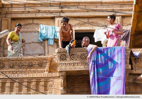 A Rajasthani family takes tea on the balcony of their carved sandstone home in the golden city of Jaisalmer, Rajasthan, Western India, 2009 by Elise Prudhomme.