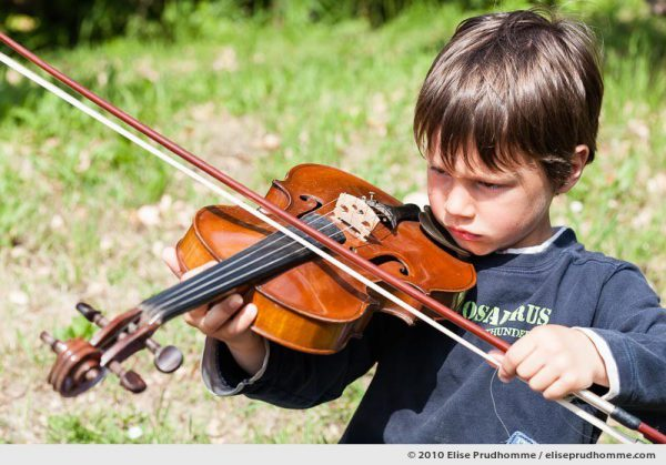Serious boy playing the violin outside in a garden, Normandy, France, 2010 by Elise Prudhomme.