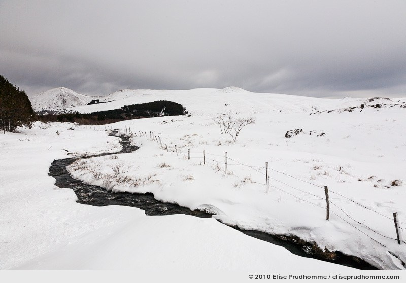 Snow covered hills and stream running through, Banne d'Ordanche, Auvergne, France, 2010 by Elise Prudhomme.