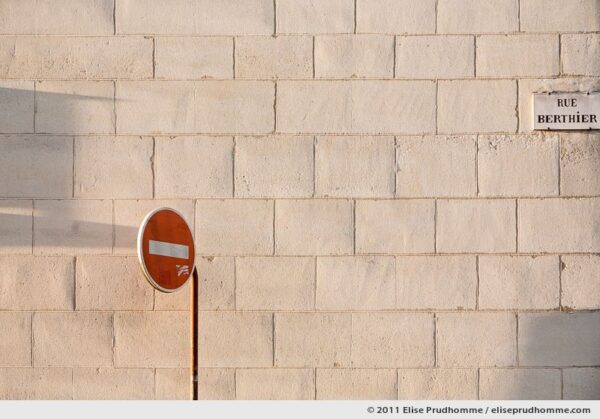 Sun setting on a stone wall and Do Not Enter sign, Rue Berthier, Versailles, France, 2011 by Elise Prudhomme.