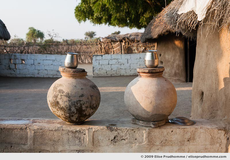 Terra cotta water jars and metal cups in a Bishnoi tribal village near Rohet, Rajasthan, Northern India, 2009 by Elise Prudhomme.