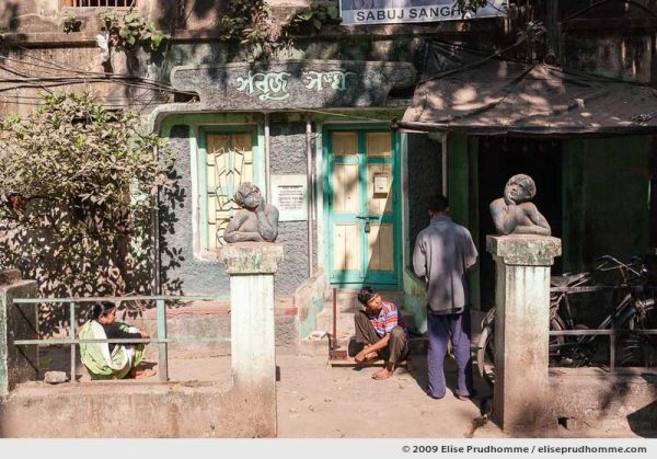 Three people conversing in a courtyard marked by two columns with statues of angels, Calcutta, Kolkata, West Bengal, India, 2009 by Elise Prudhomme.