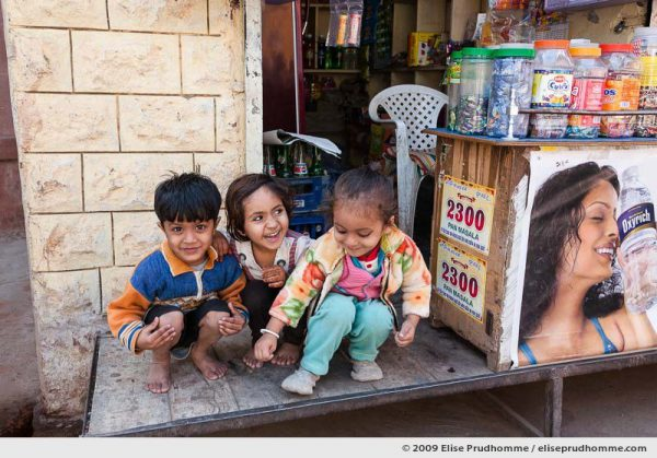 Three smiling children in front of a small store, Oisan, Rajasthan, India, 2009 by Elise Prudhomme.