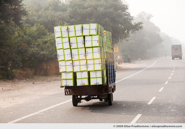 Truck overloaded with shoe boxes on the Agra Road, Uttar Pradesh, India, 2010 by Elise Prudhomme.