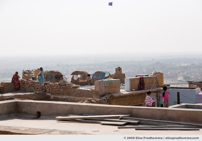 Two boys flying a kite and two women talking on the rooftops of golden city of Jaisalmer, Rajasthan, Western India, 2009 by Elise Prudhomme.