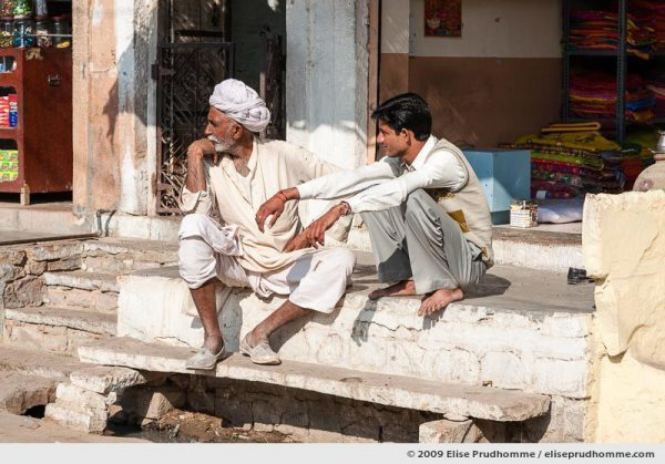 Two Indian men, one wearing traditional clothing, sitting in front of a shop in Rohet village, Rajasthan, Jodphur, India, 2009 by Elise Prudhomme.