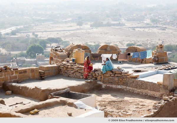 Two women talking and laundry drying on the rooftops of golden city of Jaisalmer, Rajasthan, Western India, 2009 by Elise Prudhomme.