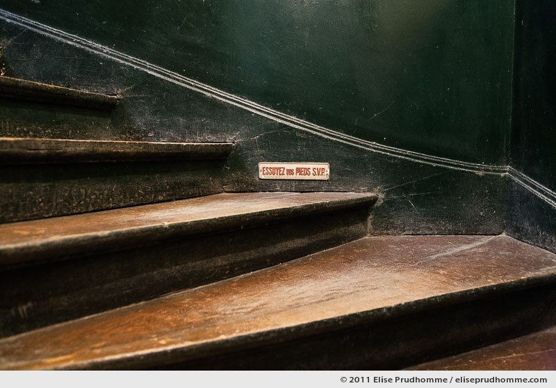 Wipe Your Feet Please sign in an old fashioned Parisian staircase, France, 2011 by Elise Prudhomme.