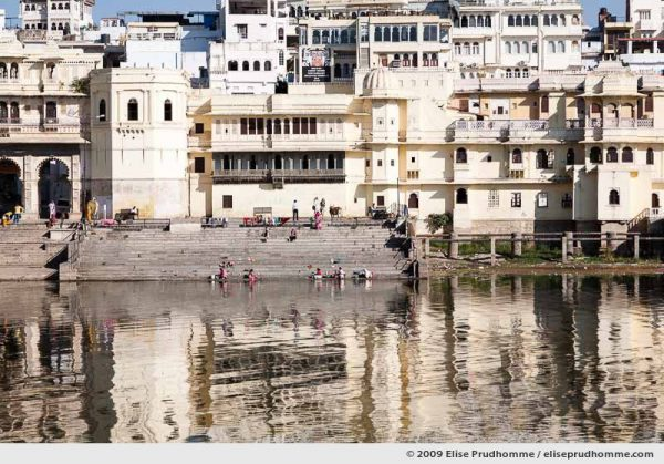 Women washing clothing in Lake Pichola Ghats in front of Udaipur City palace, Rajasthan, Northern India, 2009 by Elise Prudhomme.