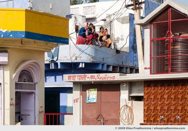 Women watching the street above a village petrol station, Rajasthan, India, 2009 by Elise Prudhomme.