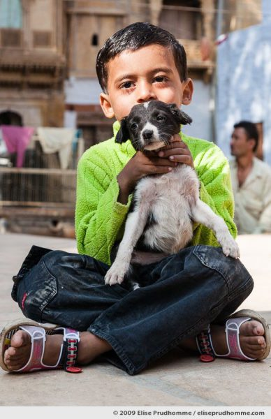 Young boy in green sweater holding a pet dog in Jaisalmer, Rajasthan, Western India, 2009 by Elise Prudhomme