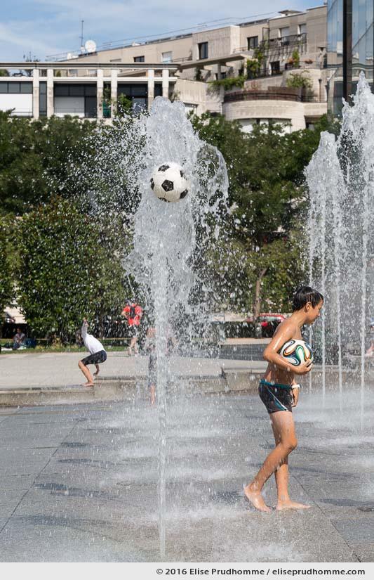 A young boy plays with a soccer ball in the water jets at Parc Andre Citroen, Paris 15th district, France. Un jeune garçon joue avec un ballon de foot dans les jets d'eau à Parc Andre Citroen, Paris 15ème arrdt, France.