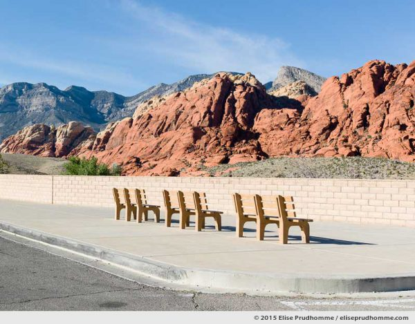 Color photograph of ochre colored visitor's benches at the scenic viewpoint overlooking Red Rock Canyon National Conservation Area, Las Vegas, Nevada, USA.  Bancs publics sans personne et vue panoramique à Red Rock Canyon, Las Vegas, Nevada, USA.