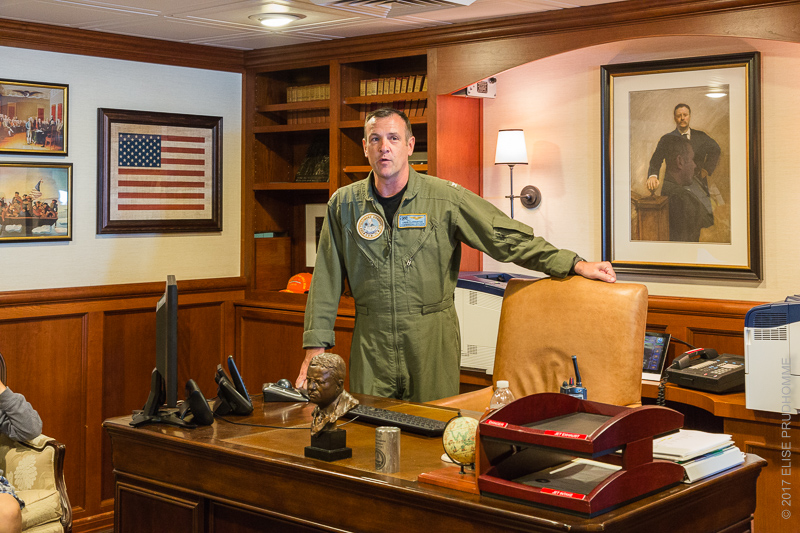 Captain Craig Clapperton in the Commanding Officer's quarters of the USS Theodore Roosevelt (CVN 71) surrounded by Theodore Roosevelt memorabilia and portrait.