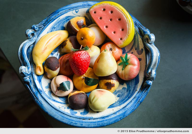 Choice of fruit shaped marzipan sweets, influenced by Silician culinary traditions, displayed in a traditional blue ceramic bowl made in Cefalu, Sicily. Frutta Martorana, fruit de marzipan sicilien fait main traditionnel dans un bol en ceramique bleu de Cefalu, Sicile.