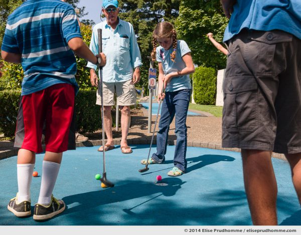 A grandfather plays minigolf with his grandchildren at Wilsonville Family Fun Center miniature golf course on a sunny clear summer day, Oregon, USA.  Un grandpère joue au minigolf avec ses petits-enfants au parcours de Golf Miniature par un jour d'été clair et ensoleillé, Wilsonville, Oregon, USA.