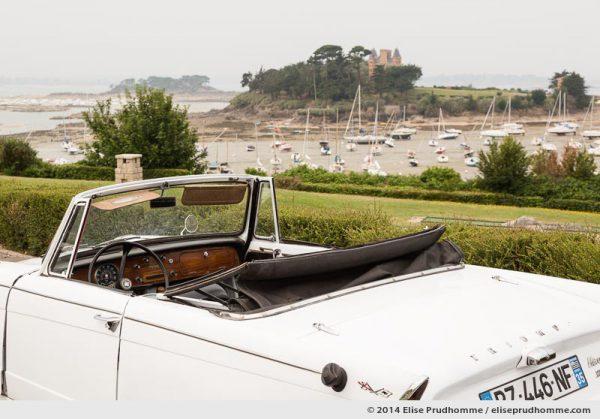 Classic car Triumph Herald Convertible 1967 to 71 and overview of the Château du Nessay, Saint Briac, Brittany, France. Voiture antique le Triumph Herald Convertible 1967 à 71 et vue du Château du Nessay, Saint Briac, Bretagne, France.