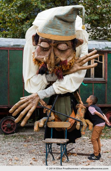 A young boy looks at a giant articulated marionnette at the Museum of Fairground Arts in Paris, France.  This unique museum presents an exceptional collection of objects from the performing and fairground arts. Un jeune garçon osculte une marionnette articulée géante au Musée des Arts Forains à Paris, France.  Cette musée unique présente une collection d'objets provenant de la patrimoine du spectacle et des Arts Forains.