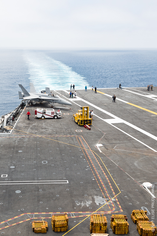 From the bridge looking down at the flight deck and the ocean wake of the USS Theodore Roosevelt on June 19, 2017.