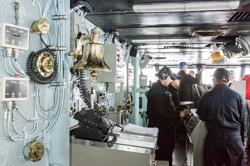 Interior shot of the bridge and a 20-year old sailor at the helm of the USS Theodore Roosevelt.