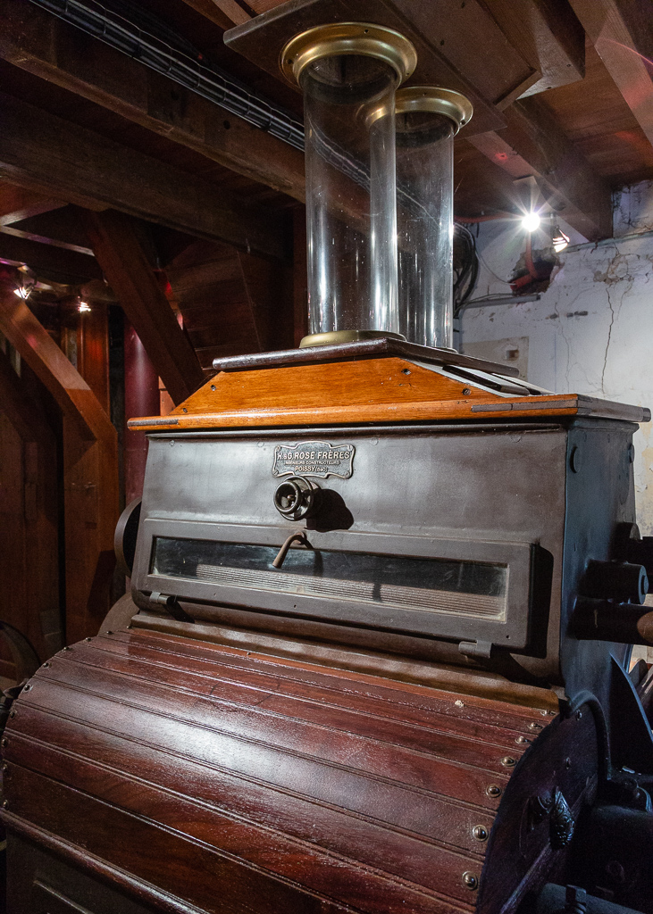 This roller mill, built in the workshops H. & G. Rose brothers of Poissy, is part of the crushing equipment of Saint-Gabriel Flour Mill. Its hull of metal and wood envelops cast iron cylinders that grind wheat grains falling from glass supply globes. Several successive passages between different cylinders are necessary to obtain a white flour.